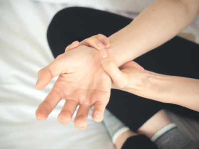 Mlada ženska si stiska zapestje, zaradi bolečine v zapestju, ime tudi mravljince v roki.